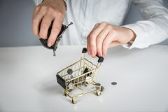 Hand holding a coin with pile of coin in the shopping cart on white and grey background. Symbolic photo for purchasing power and consumption stock photos