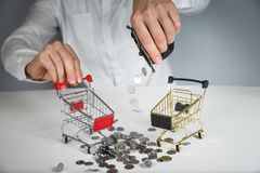 Hand holding a coin with pile of coin in the shopping cart on white and grey background. Symbolic photo for purchasing power and consumption royalty free stock photo
