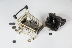 Hand holding a coin with pile of coin in the shopping cart on white and grey background. Symbolic photo for purchasing power and consumption stock images