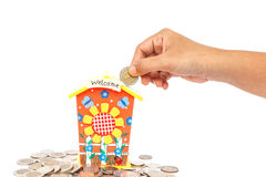 Hand holding coin and put in piggy bank isolated on white backgr Royalty Free Stock Images