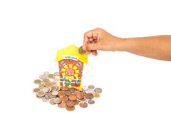 Hand holding coin and put in piggy bank isolated on white backgr Stock Photo