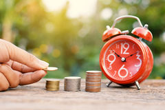 Hand holding coin with red alarm clock  on old wood Royalty Free Stock Photos