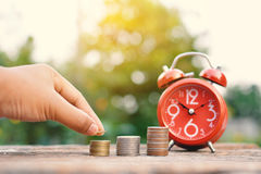 Hand holding coin with red alarm clock  on old wood Royalty Free Stock Photography