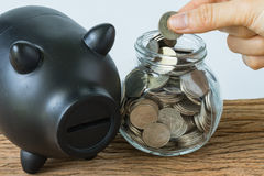 hand holding coin to put in jar and black piggy bank as financial saving or mortgage house loan concept stock photo