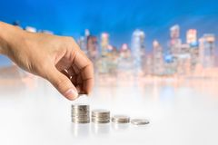Hand holding coins against Cityscape background. Hand holding coins against mean someone saving money for better future stock photos