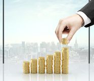 Hand holding coins. Businessman hand holding gold coins in office Royalty Free Stock Image
