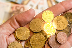 A hand holding coins witheurobanknotes at the background Royalty Free Stock Image
