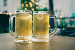 Hand holding cold beer glass on a bar scene in the background royalty free stock photography