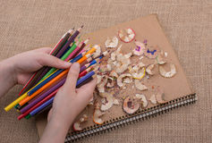 Hand holding Color Pencils over a notebook Royalty Free Stock Photos