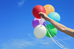 Hand Holding colorful Balloons against blue sky, close-up. Freedom, happiness, carefree concept Royalty Free Stock Photo
