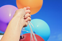 Hand Holding colorful Balloons against blue sky, close-up. Freedom, happiness, carefree concept Stock Photo