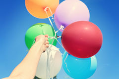 Hand Holding colorful Balloons against blue sky, close-up. Freedom, happiness, carefree concept Stock Image