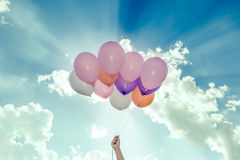 Hand holding colorful balloons on blue sky background Stock Photo