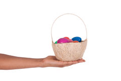 Hand holding colorful Easter eggs in the basket Stock Photos