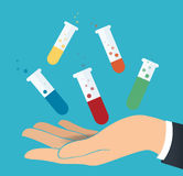 Hand holding colorful laboratory filled with a clear liquid and blue background Royalty Free Stock Photos