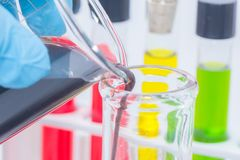 Hand holding colorful liquid in Beaker. With glove stock photo