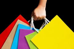Hand holding colorful paper bags