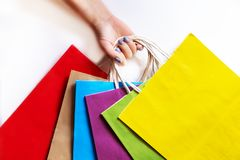 Hand holding colorful paper bags on a white background