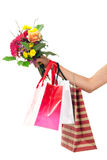 Hand holding colorful shopping bags and flowers Royalty Free Stock Photo