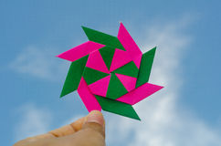 Hand holding colorful weathercock origami folding paper Stock Image