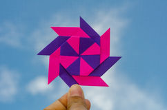 Hand holding colorful weathercock origami folding paper Stock Photos