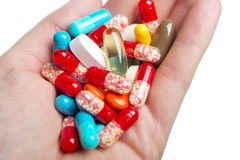 A hand holding coloured pills and capsules. Stock Images