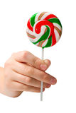 Hand holding colourful lollipop Royalty Free Stock Photos