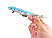 A hand holding a comercial aircraft model. On white background Royalty Free Stock Photo
