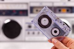 Hand holding compact audio cassette tape royalty free stock photo