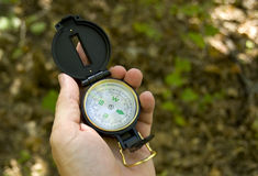 Hand holding a Compass. A man's hand holding an engineer's compass on a hiking trail Royalty Free Stock Photography