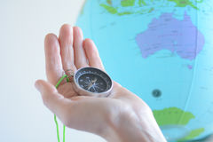 Hand holding a compass with Australia on a globe Royalty Free Stock Image