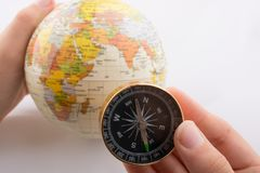 Hand holding a compass and a globe. On white background Stock Photos