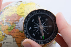 Hand holding a compass and a globe Royalty Free Stock Photo