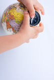 Hand holding a compass and a globe Royalty Free Stock Photography
