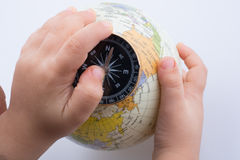 Hand holding a compass and a globe Stock Photos