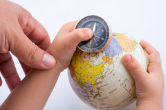 Hand holding a compass and a globe Stock Photo
