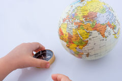 Hand holding a compass and a globe Royalty Free Stock Photos