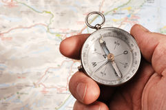 Hand holding compass, map (out of focus) in the background Stock Photo