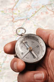 Hand holding compass, map (out of focus) in the background Stock Images