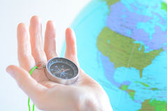 Hand holding a compass with North America on a globe. In the background. Travel lifestyle concept. copy space royalty free stock images