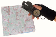 Hand holding a compass over a map Stock Photo