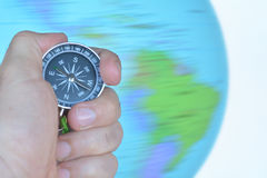 Hand holding a compass with a spinning globe Stock Images