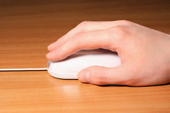 Hand holding computer mouse. A human hand holding a white computer mouse on wooden table Stock Photography