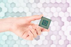 Hand Holding Computer Processor Chip On Light Hexagon Background. With Blue Purple Tint Stock Image