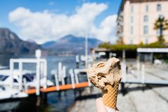 Hand holding cone of Gelato, Italian ice-cream with blur background of a landscape view of Lake Como in Italy. Royalty Free Stock Images