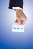 Hand holding contact us card. Business man hand holding contact us card Stock Photo