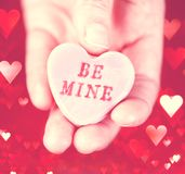 Hand holding conversation heart - Be Mine. Hand holding a conversation heart - Be Mine royalty free stock photo