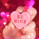 Hand holding conversation heart - Be Mine. Hand holding a conversation heart - Be Mine royalty free stock image
