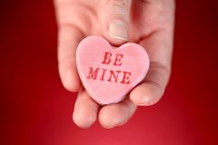 Hand holding conversation heart - Be Mine. Hand holding a conversation heart - Be Mine royalty free stock photography