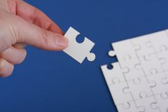 Hand holding corner of jigsaw. Detached corner of plain white jigsaw puzzle being held in someones hand with the jigsaw puzzle out of focus on a blue background Stock Photo